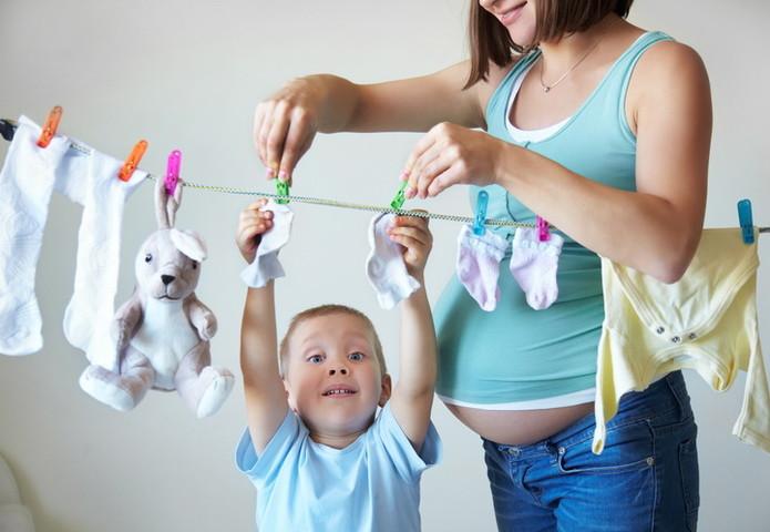 беременная мать и ребенок вешают белье