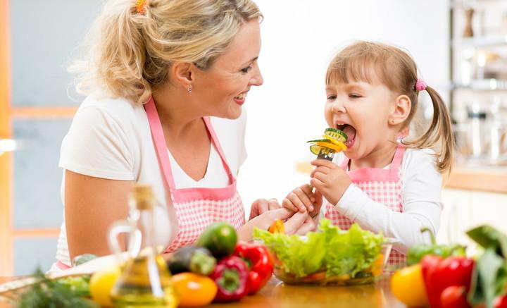 девочка ест свежие овощи