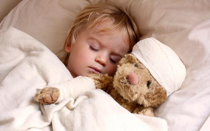 ребенок спит в кровати с игрушкой