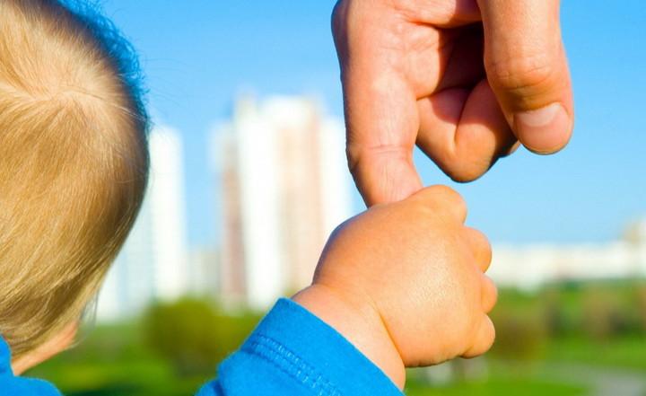 ребенок держит отца за палец