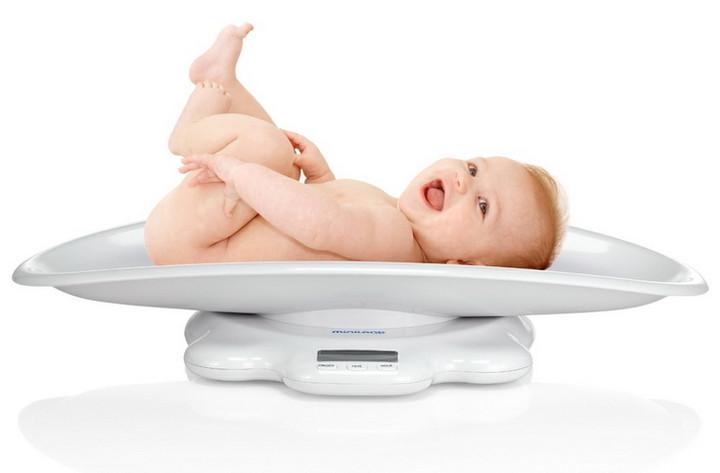 младенец лежит на весах